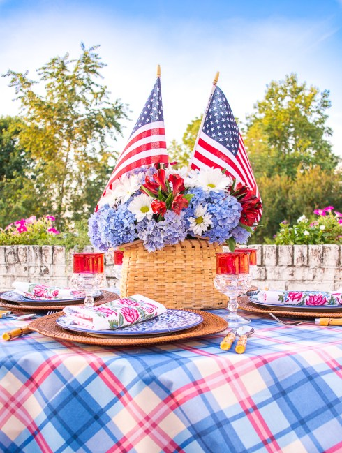 Handmade basket centerpiece filled with blue hydrangea, daisies, and American flags