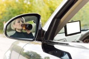 Female driver drinking as she drives