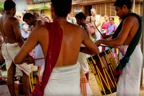 Priest playing traditional musical instruments during the ceremony