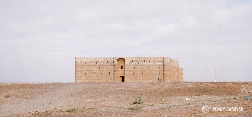 Qasr Kharana stands isolated on the flat desert landscape.