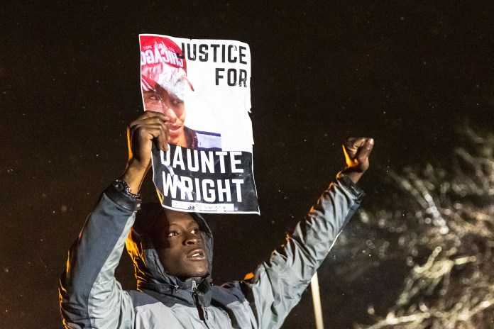 """A demonstrator holds a photo of Daunte Wright and shouts """"Don't shoot"""" at the police after curfew as people protest the death of Daunte Wright"""