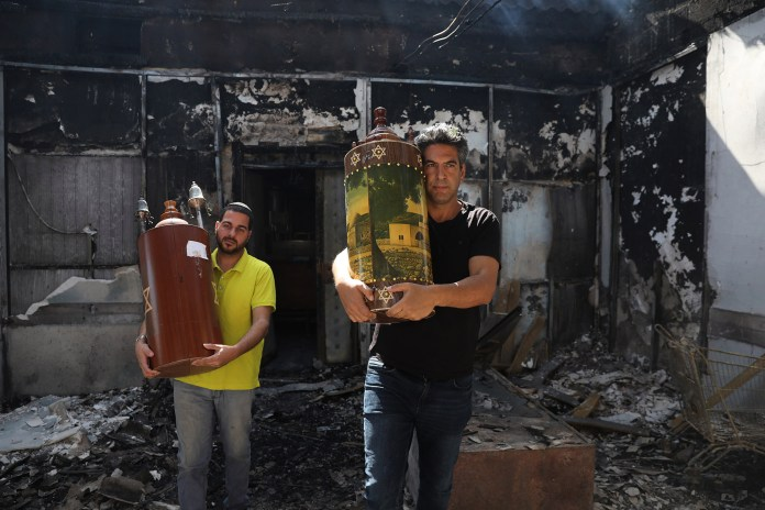 Jewish residents take out a Torah scroll from a burned synagogue following overnight riots between Arab and Jewish residents in Lod, Israel.