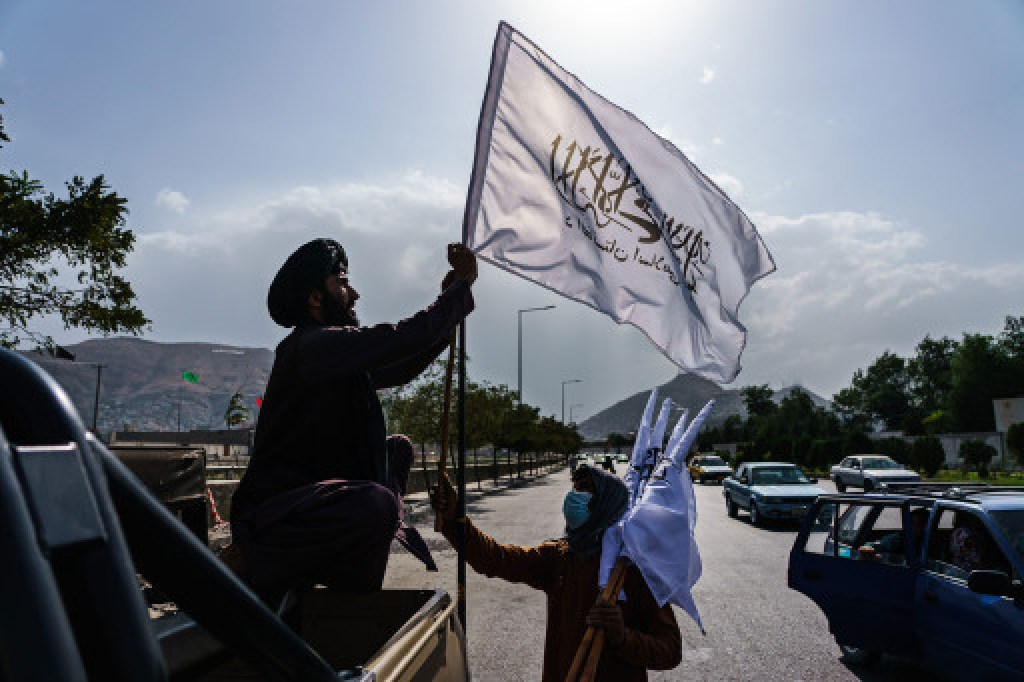 A Taliban leader putting a flag up on his vehicle in Kabul, Afghanistan on August 20, 2021.
