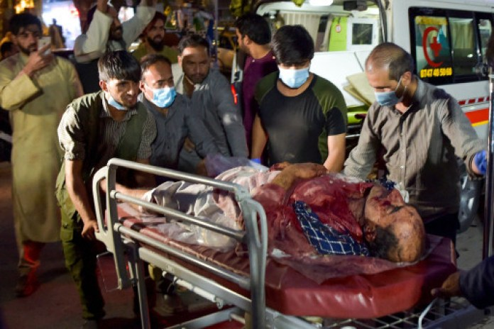 Volunteers and medical staff bring an injured man for treatment after the two explosions.