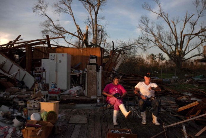 A couple sits outside the ruins of their house in Pointe-aux-Chenes, Louisiana.