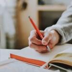 A hand holding an orange pen