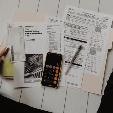 Various tax forms and a calculator on a table in between a person's arms