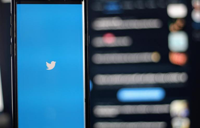 A phone with the Twitter logo on the screen, with a blurry Twitter timeline in the background