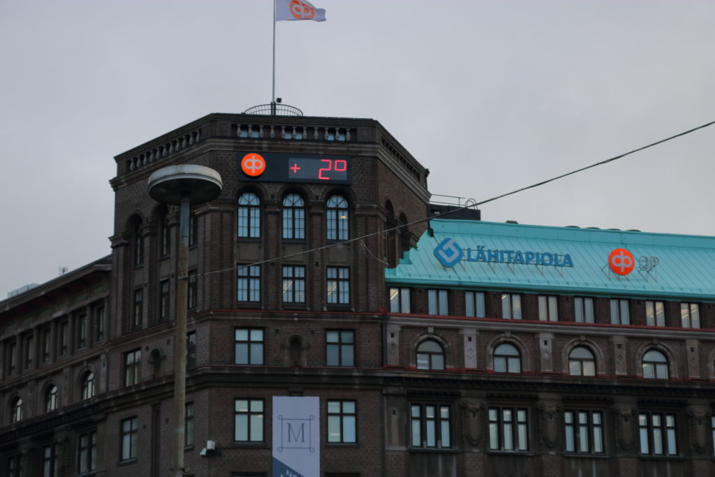 An old building with a digital sign displaying temperature