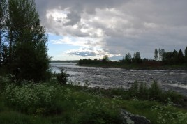 River with a greenery in the foreground and storm clouds