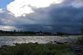 Dark storm clouds above a river and a Swedish resort