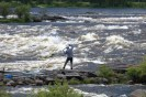 A man in a chequered shirt dip net fishing over a coursing river
