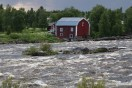 A barn-like Swedish building with a coursing river in the foreground