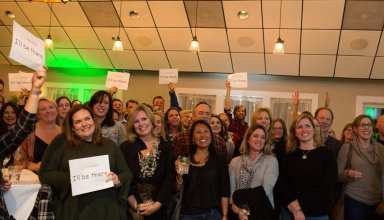 "A sold-out crowd of more than 130 community members from Merrimac, Groveland and West Newbury hold up signs pledging ""I'll Be There"" on voting day. They filled Michael's Harborside in Newburyport at the We Are Pentucket campaign kickoff party on Oct. 25, 2018. (Courtesy Photo)"