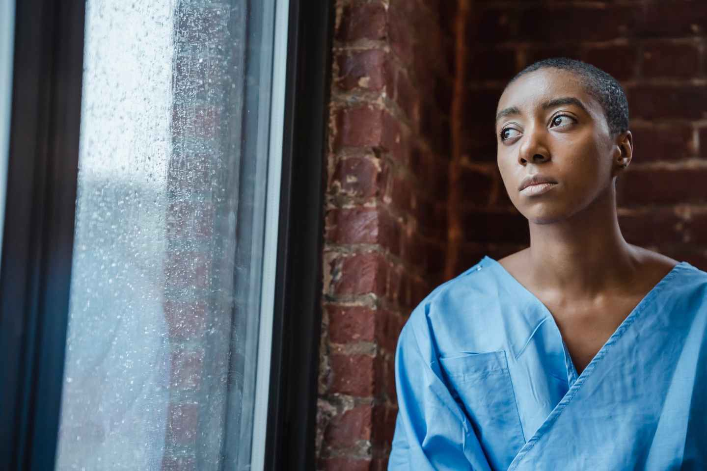 thoughtful androgynous black woman looking at window in rainy day