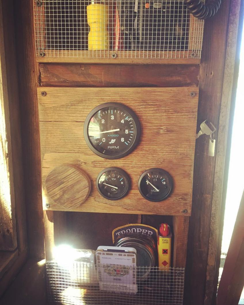 Radio shelf, engine gauges, and tobacco shelf from top to bottom on the shantyboat