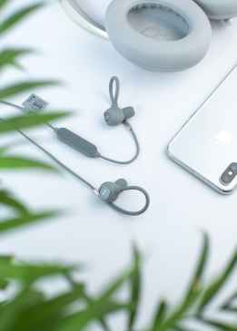 contemporary earphones and headphones on white table near smartphone