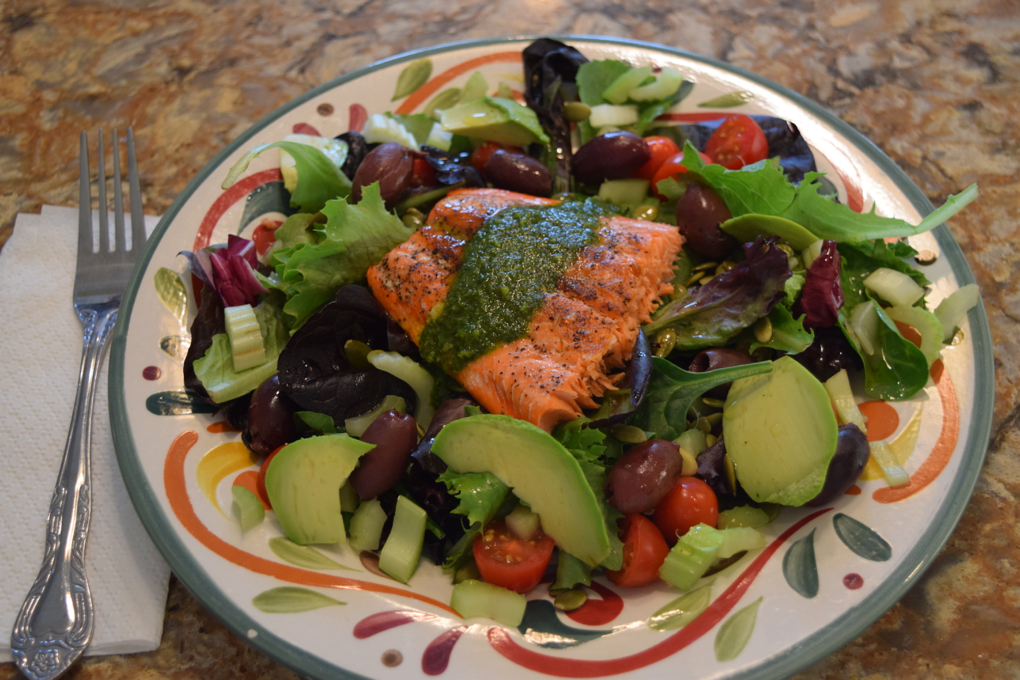 Photo of salmon on top of green salad with avocado, tomatoes, celery and black olives