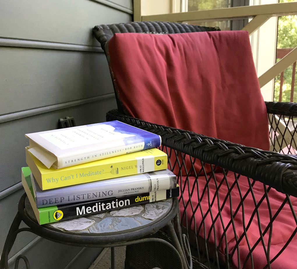 Photo of stack of meditations sitting beside chair with red cushions
