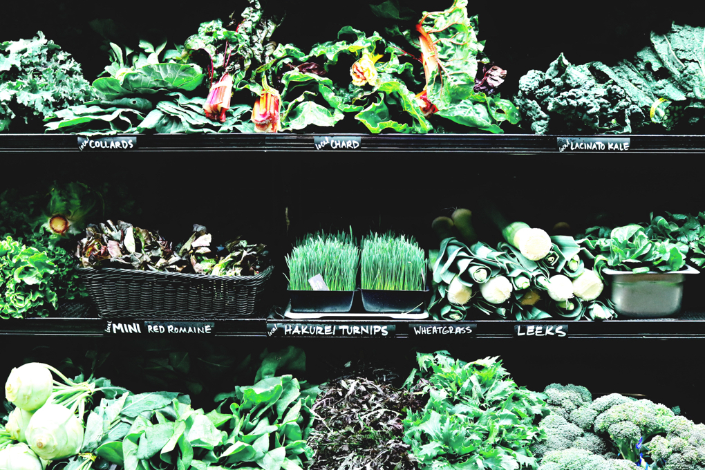 Photo of different types of greens on grocery store shelf that serve as healing foods