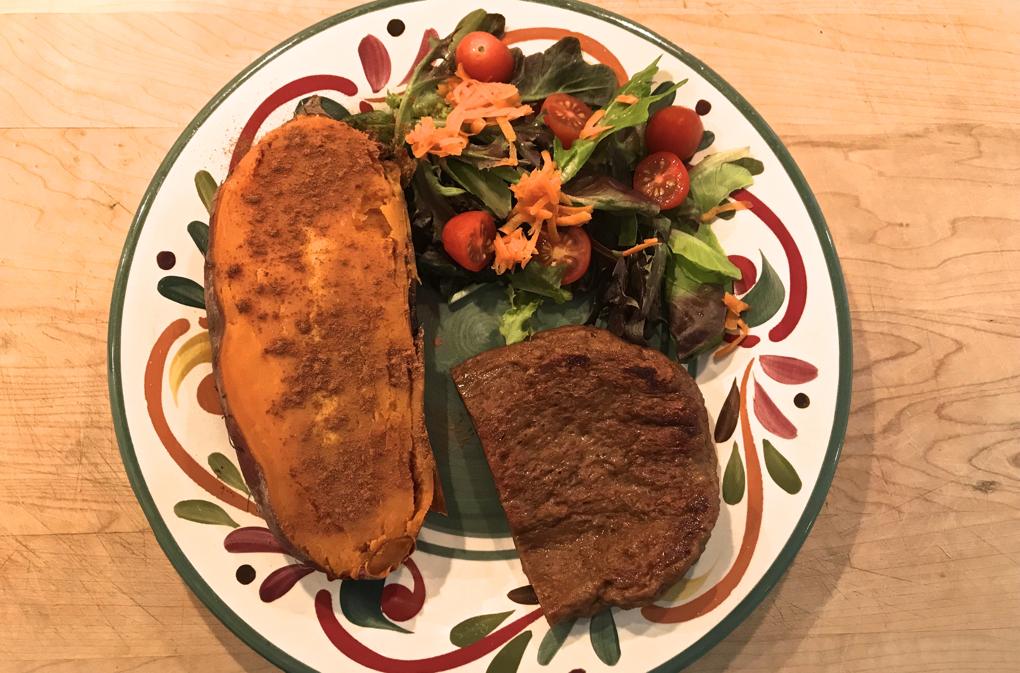 Photo of Vegan Seitan Steak on colorful plate with sweet potato and salad