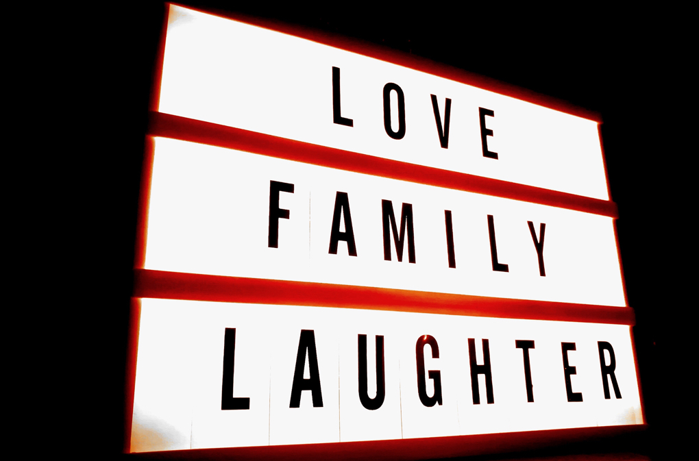 """Photo of red and white sign with black lettering that says """"Love, Family, Laughter"""""""