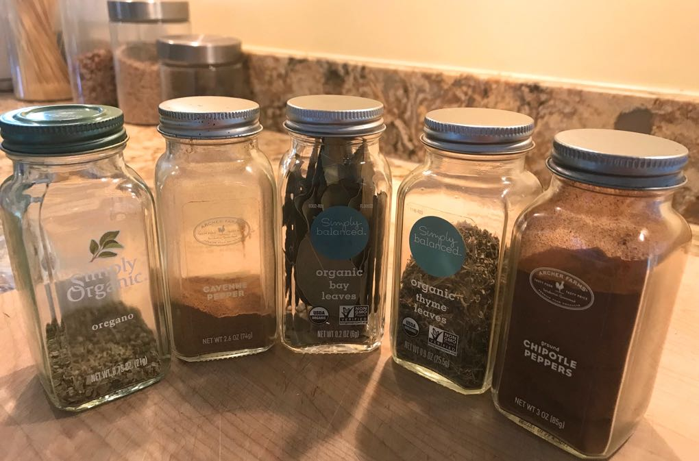 Photo of glass bottles of spices ready for cooking sitting on the counter