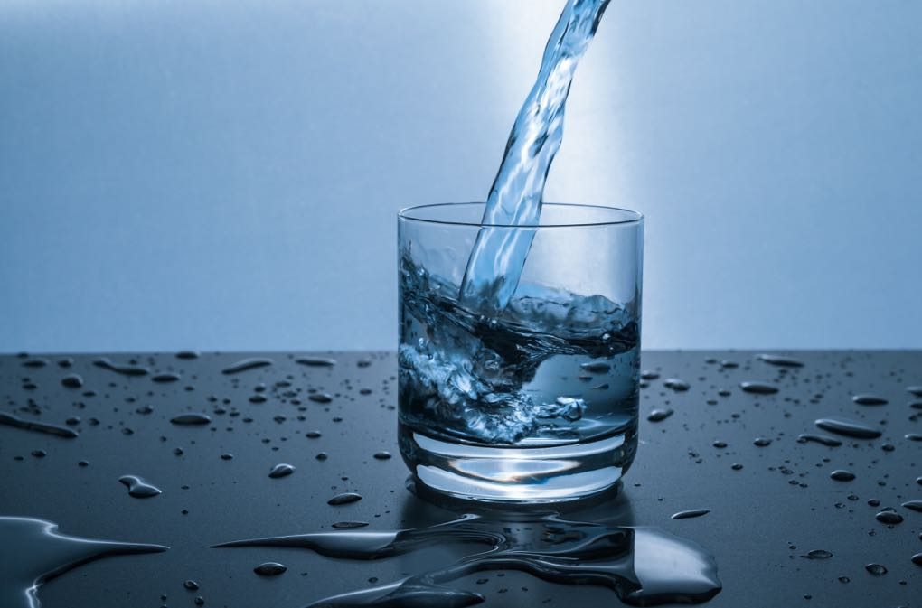Photo of water being poured into a glass as an example of steps to take toward Real Health