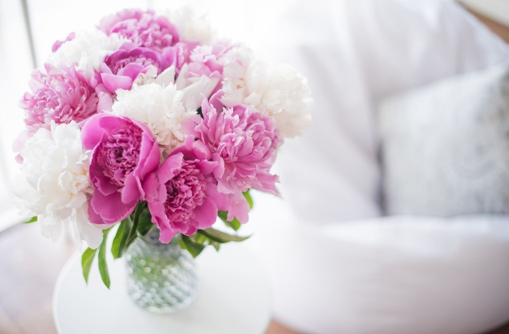 Photo of pink and white flowers next to a white chair