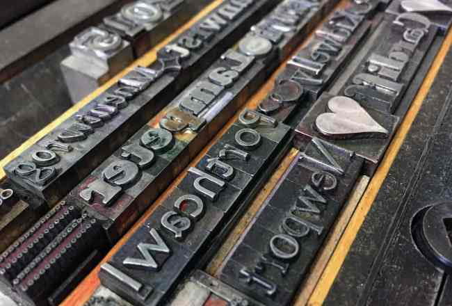 Closeup photograph of metal letterpress type set in press bed ready for printing