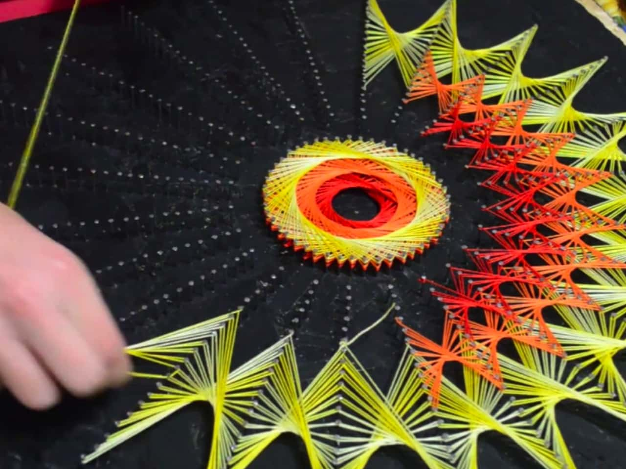 Closeup photo of creative string art on black foam board using green and red neon coloured string