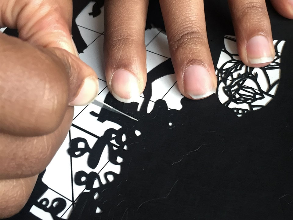 closeup of using a scalpel for a detailed paper cut craft project