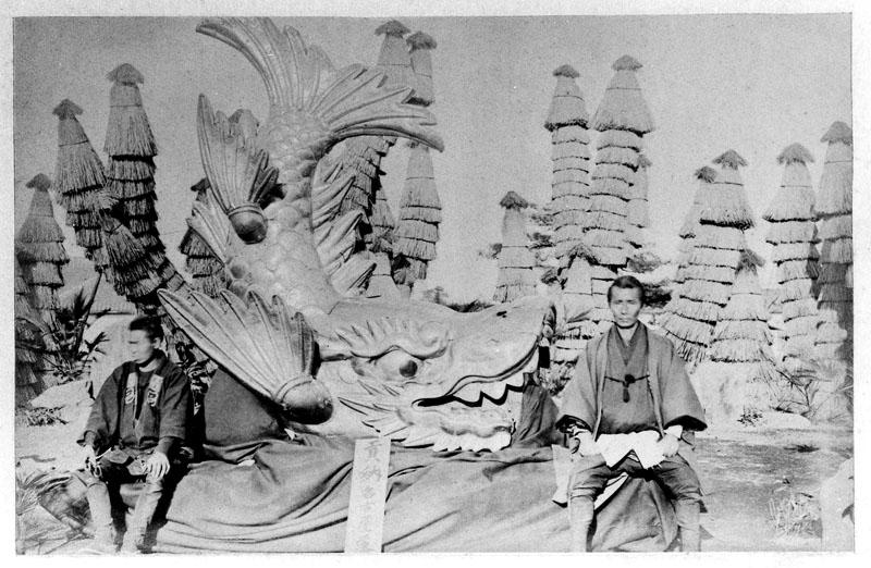 Photo de deux japonais assis de chaque côté du shachihoko envoyé à Vienne en 1873