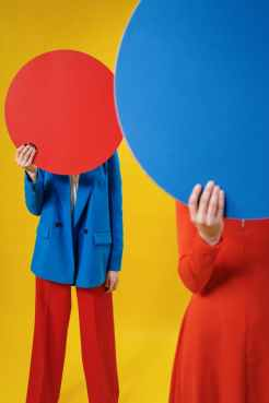 anonymous trendy ladies covering faces with colorful sheets in studio