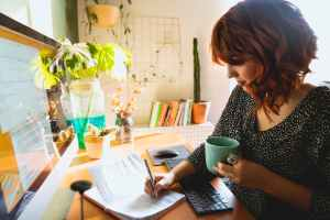 woman writing on her notebook while holding a cup