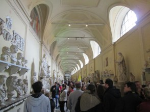 A long hallway full of busts and statues.