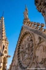 Tímpano triangular con un óculo inscrito decorado con bajorrelieves y trabajos de tracería, coronado por una imagen de la Inmaculada Concepción como remate de la portada que da a La Almudaina