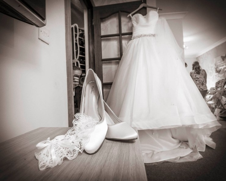 Wedding shoes and dress hanging
