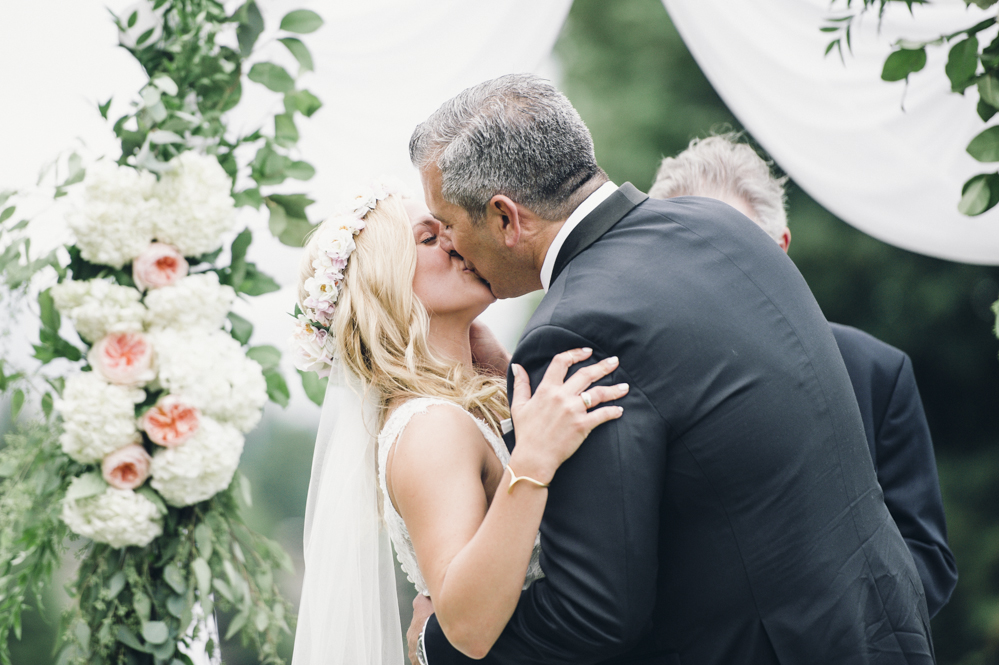 Glen Acres Golf Club wedding in Seattle | First kiss under white arch with blush and white blooms | Perfectly Posh Events, Seattle Wedding Planner | Barrie Anne Photography | Butter & Bloom