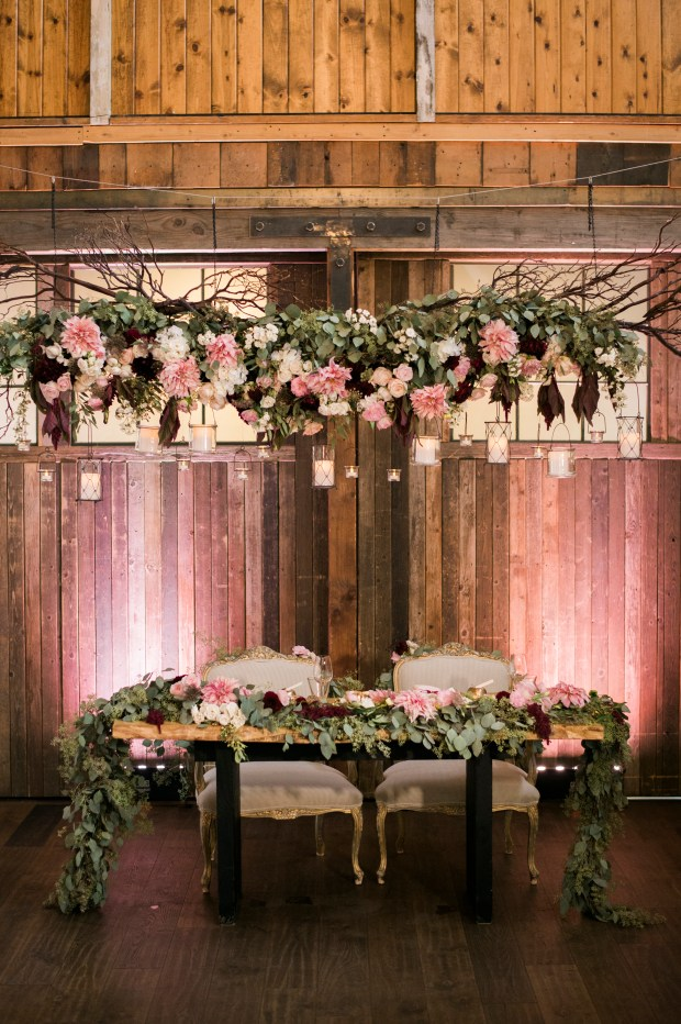 Sodo Park Wedding in Seattle | Hanging floral and branches installation over sweetheart table. Pink, burgundy, and cream flowers with branches | Perfectly Posh Events | Kimberly Kay Photography | Floressence