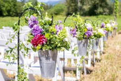 Galvanized buckets on shepherds hooks with lush green, purple, and pink florals as markers down ceremony aisle | Meadowbrook Farm Wedding, Snoqualmie, WA | Perfectly Posh Events, Seattle Wedding Planner | Down to Earth Flowers | Sasha Reiko Photography | Jesse + Wes Wedding // © Sasha Reiko Photography