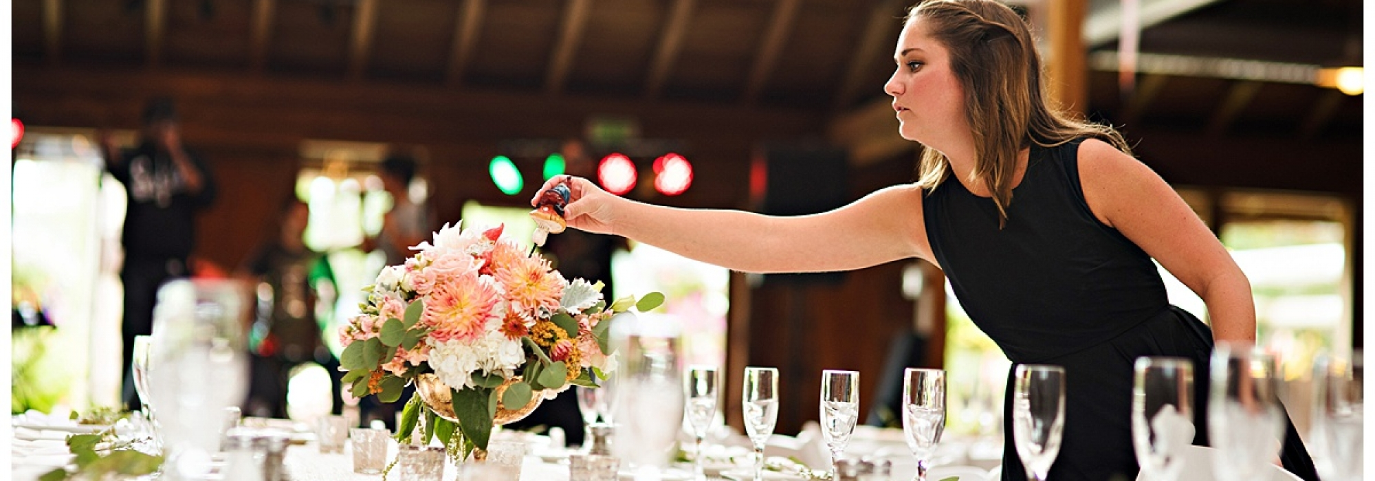 Portland wedding planner Bridget Forster putting the finishing touches on a centerpiece at a wedding | Photo by Barbie Hull Photography