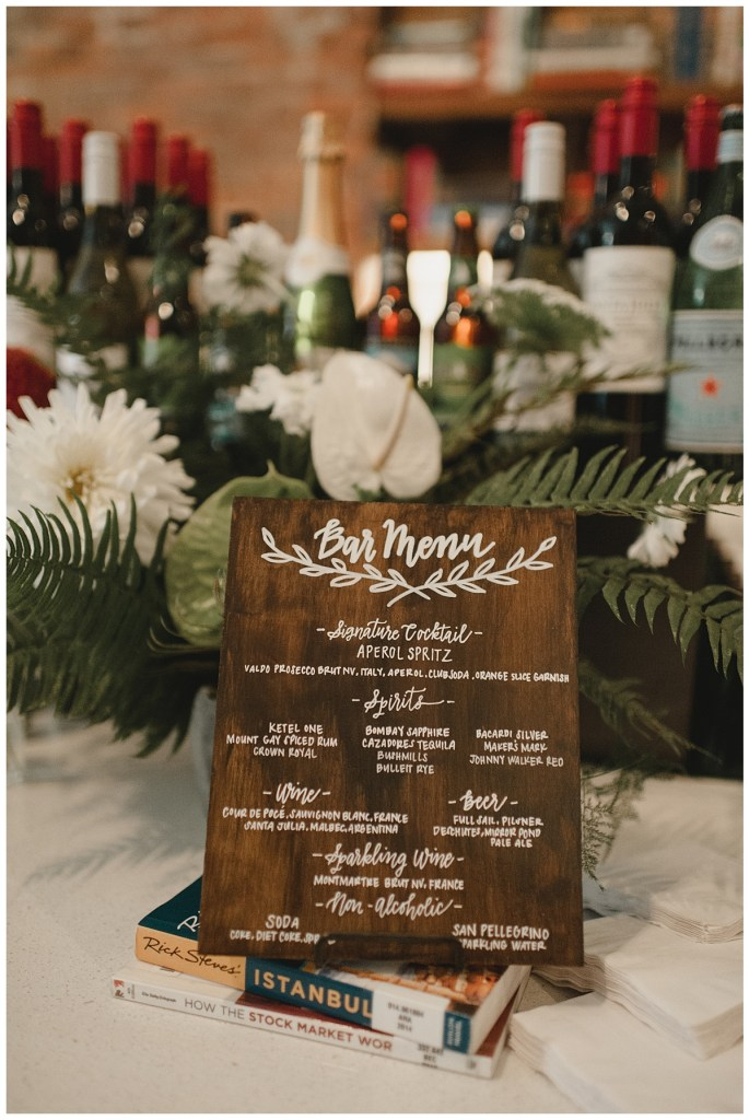Custum wedding cocktail menu hand painted on rustic wood board accessorized with white flowers and green ferns, Axis Pioneer Square wedding, Seattle wedding, planning and design by Perfectly Posh Events, Seattle Wedding Planner, Photo by Carina Skrobrecki