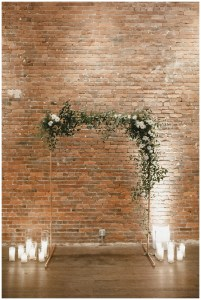 Indoor wedding altar decorated with white flowers, greenery, and white candles sits in front of an urban brick wall, Axis Pioneer Square wedding, Seattle wedding, planning and design by Perfectly Posh Events, Seattle Wedding Planner, Photo by Carina Skrobrecki