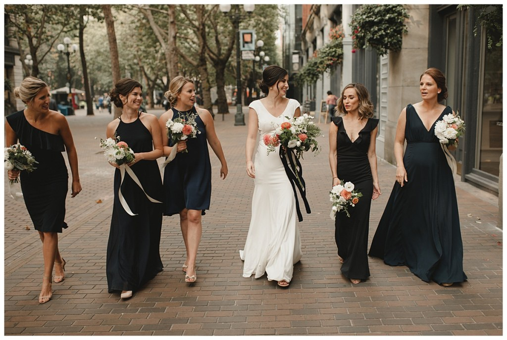 Bride walks through Seattle's Pioneer Square with her bridesmaids in navy dresses, Axis Pioneer Square wedding, Seattle wedding, planning and design by Perfectly Posh Events, Seattle Wedding Planner, Photo by Carina Skrobrecki