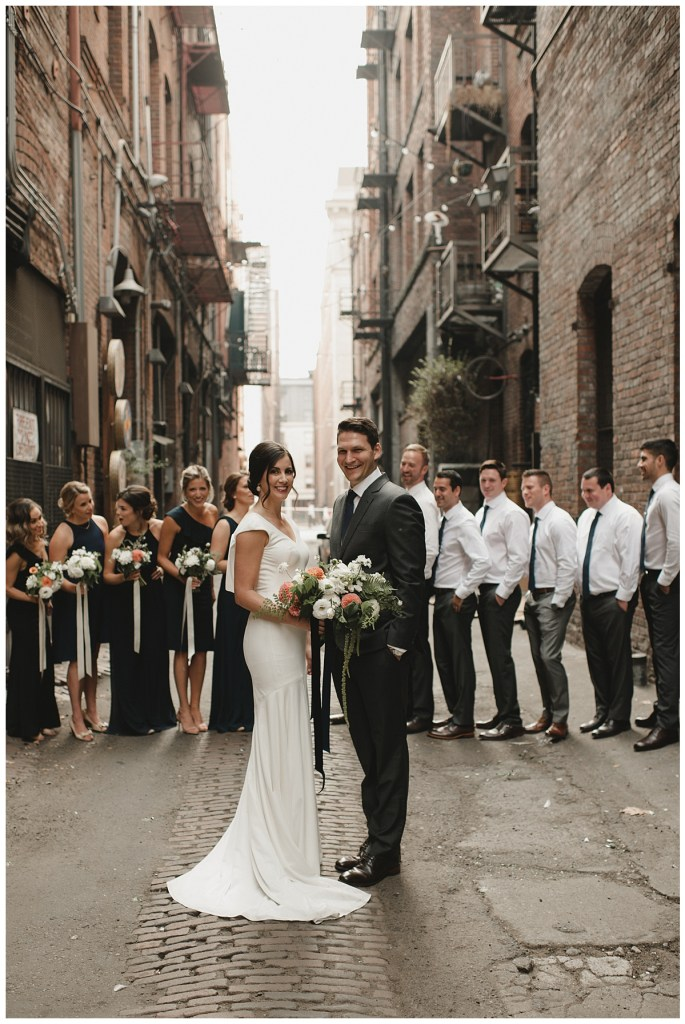 Bride and groom pose together in urban alleyway with bridesmaids and groomsmen in background, Axis Pioneer Square wedding, Seattle wedding, planning and design by Perfectly Posh Events, Seattle Wedding Planner, Photo by Carina Skrobrecki