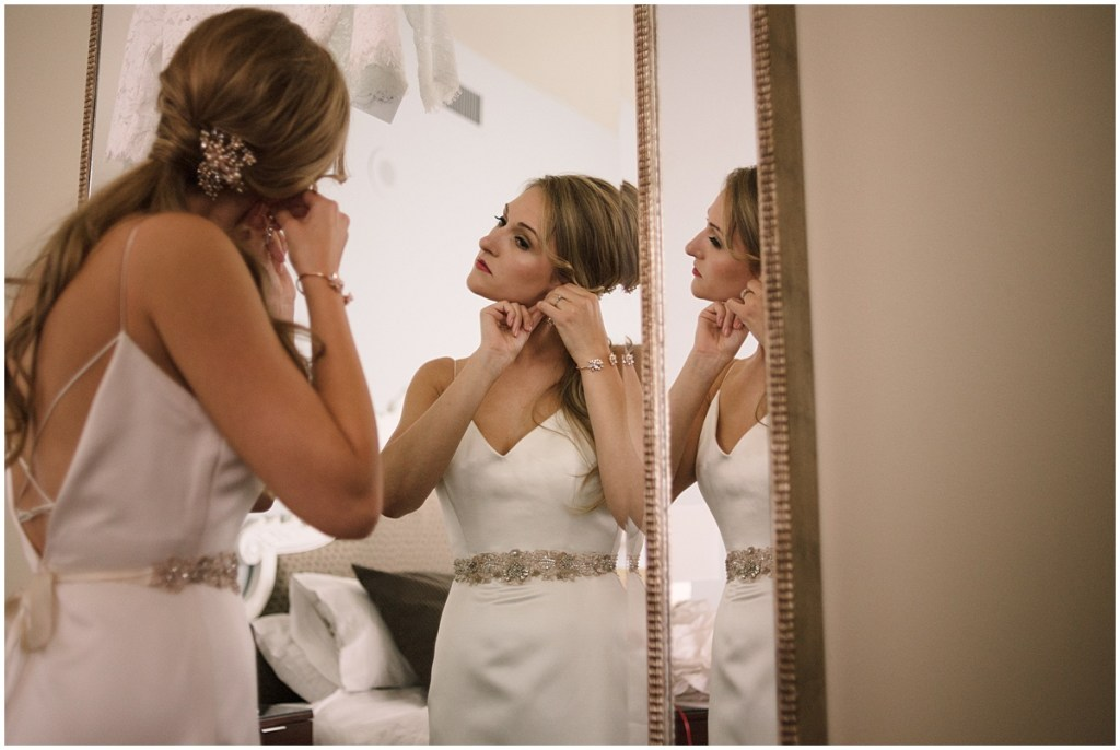 Bride in white satin gown puts on earrings before her wedding, Axis Pioneer Square wedding, Seattle wedding, Perfectly Posh Events, Seattle Wedding Planner, Photo by Roland Hale