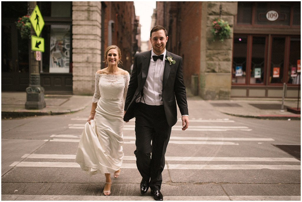 Newlywed bride and groom hold hands while strolling through Seattle