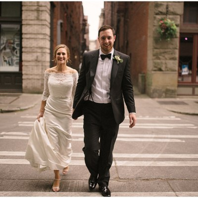 Newlywed bride and groom hold hands while strolling through Seattle's Pioneer Square neighborhood, Axis Pioneer Square wedding, Seattle wedding, Perfectly Posh Events, Seattle Wedding Planner, Photo by Roland Hale