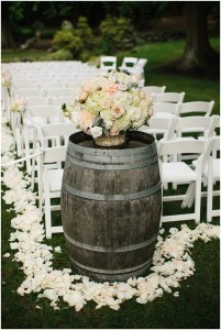 An ivory and blush floral bouquet atop a wine barrel anchors a wedding ceremony aisle, Seattle wedding, Perfectly Posh Events wedding planning and design, Seattle and Portland Wedding Planner, Photo by Lucid Captures Photography